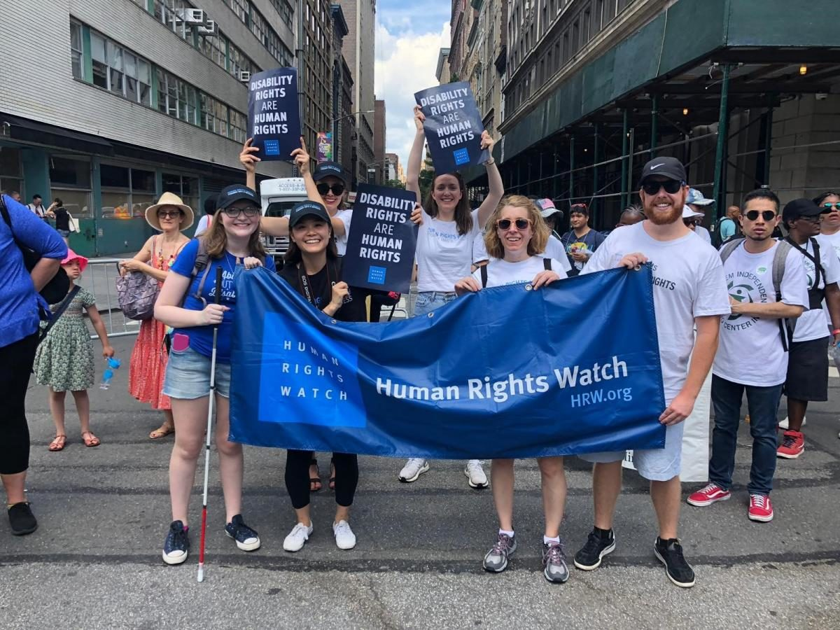 students hold banner at a disability pride parade