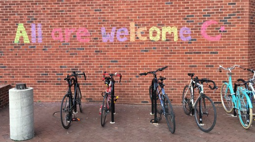 Bicycles parked outside brick building with the words written above them
