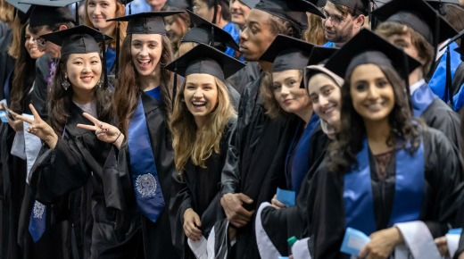 A graduation photo of six students wearing caps and gowns