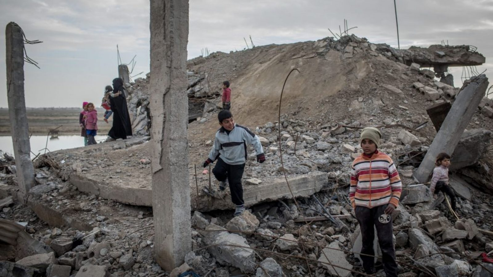 CHILDREN PLAY AMID RUBBLE ON FEBRUARY 16, 2019 IN HAJIN, SYRIA. AERIAL BOMBARDMENTS HAVE POLLUTED GROUNDWATER AND CREATED SEVERE AIR POLLUTION. EXPLOSIVE WEAPONS LEAVE A HEAVY TOXIC FOOTPRINT BEHIND FOR CIVILIANS WHO HAVE ALREADY ENDURED YEARS OF BOMBING. SOURCE: CHRIS MCGRATH/GETTY IMAGES