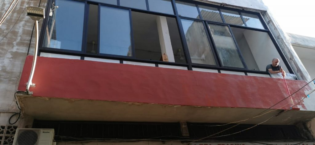 A man paints the outside of Traboulsi's studio with red paint.